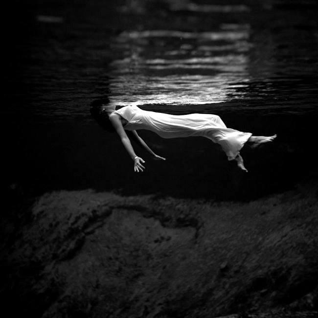 Bella mujer en el agua con la cara fuera