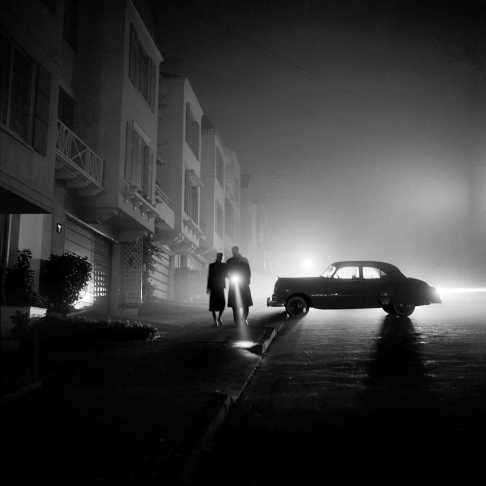 pareja con coche y linterna en la noche